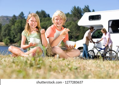 Children in countryside on motor home vacation eating breakfast