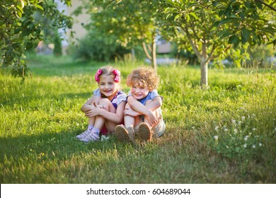 children couple in the apple garden in summer early morning, sunrise, sunset, evening light, greenery background