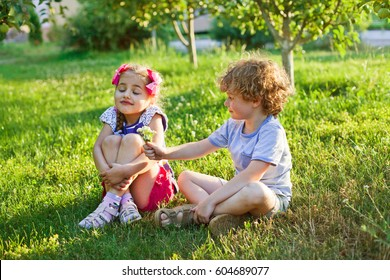 children couple in the apple garden in summer early morning, sunrise, sunset, evening light, greenery background