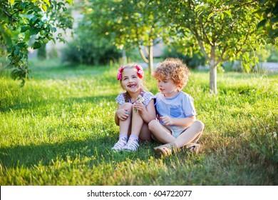 children couple seating in the apple garden, sunrise, sunset warm light, summer morning,