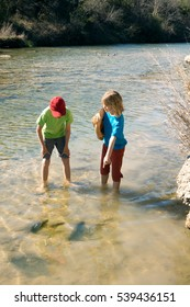 Children curiously looking at the fossilized dinosaur tracks in the river. White Blaff Creek,  Dinosaur Valley State Park, Glen Rose, Texas