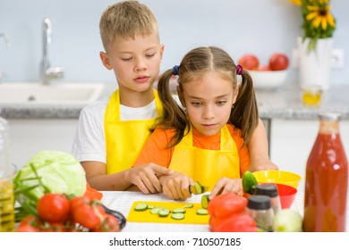 Children cut cucumbers for vegetable salad