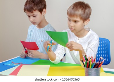 Children cutting colored paper with scissors at the table