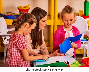 Children cutting paper in class. Kids development and social lerning children in school. Children's project in kindergarten. Small group girls with teacher together.