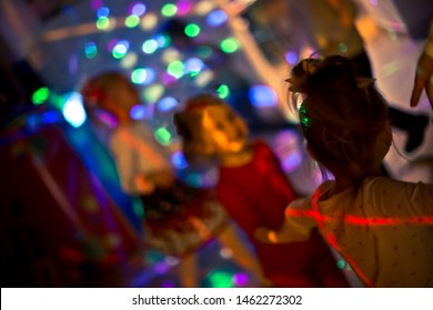 Children dance at Christmas party in blue LED lights room. Laser and neon show at child's birthday. Happy childhood. Animators at children's party. Baby disco. Selective focus