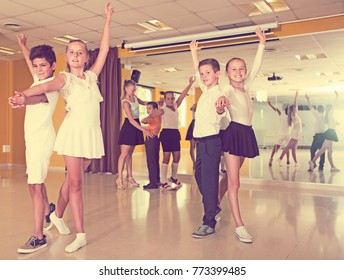 Children in dance class learning new movements, smiling and having fun