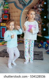 Children dance in the room. Two sisters. The concept of Christmas and New Year.