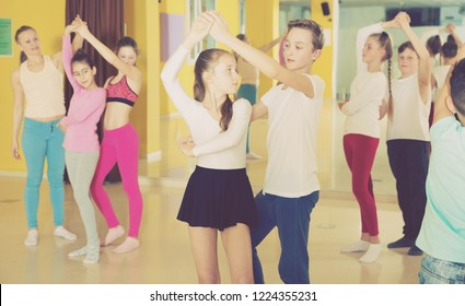 Children dancing rock-and-roll in pairs in choreography class with female trainer