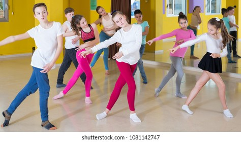 Children dancing synchronous group choreography with female coach in dance hall