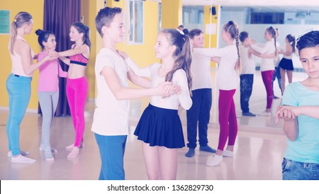 Children dancing together slow ballroom dances in pairs in choreography class with female trainer