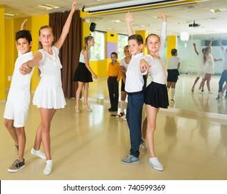 Children are dancing waltz in class.