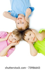 Children in different T-shirts lie on a floor to keep for ears, a white background