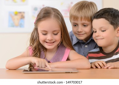 Children with digital tablet. Cheerful children looking at the digital tablet and smiling