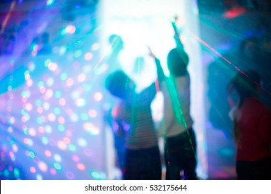 Children at a disco during the laser show with colorful rays lighting, Selective focus