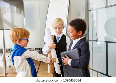 Children disguised as business people shake hands as a greeting or as a thank you