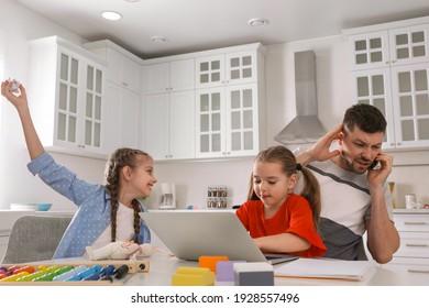 Children disturbing stressed man in kitchen. Working from home during quarantine
