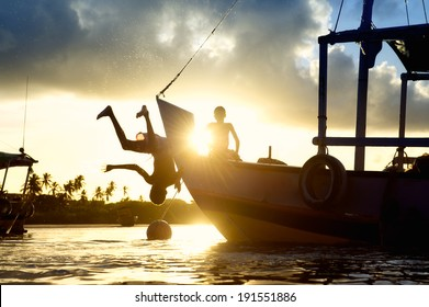Children diving in sunset silhouettes from the bow of a boat in the northeast Nordeste coast of Brazil