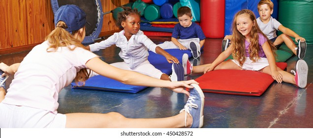 Children doing gymnastics in gym of preschool with nursery teacher
