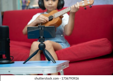 Children doing an online course to learn how to play the Ukulele,He is sitting on the sofa at home playing the Ukulele in front of the telephone while listening to the lessons.
