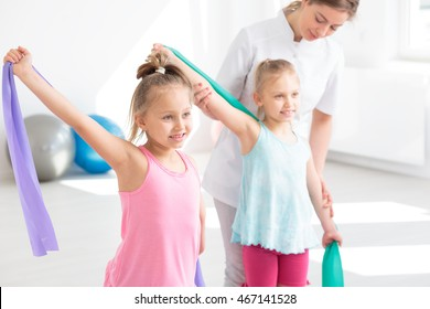 Children doing stretching exercise with young female physiotherapist