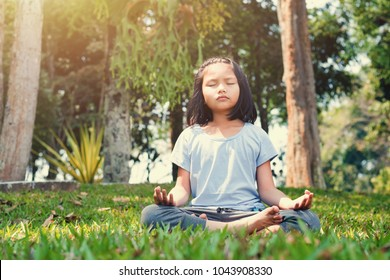 children doing yoga on grass with sunshine in the park