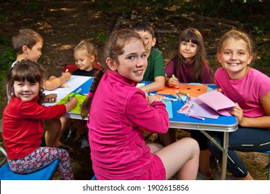 Children draw in nature. Lots of colored papers and pencils on a blue table. Boys and girls play outdoors. Drawing lesson in the park. Rest in a tent camp in the summer.