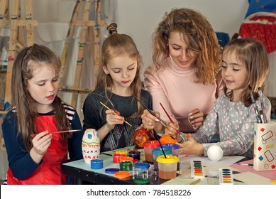 children draw at the table with the teacher. paint the mold with paints, hands in paint