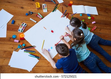 children draw together on a large sheet of paper