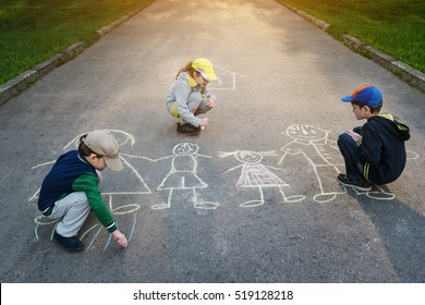 Children is drawing happy family on asphalt in spring park.