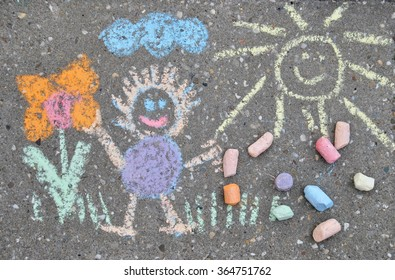 children drawing on a sidewalk made with chalk crayons