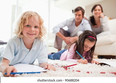 Children drawing while their parents are in the background in a living room