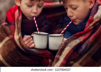 Children drink hot chocolate under warm blanket in winter forest.