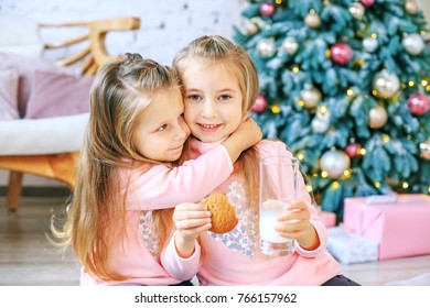 Children drink milk and eat oatmeal cookies. Girls hugging. Breakfast. Concept New Year, Merry Christmas, holiday, vacation, winter, childhood.