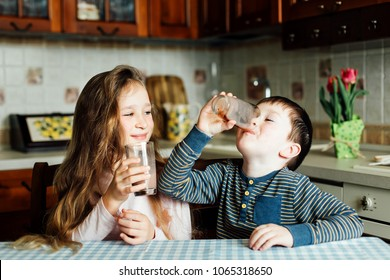 Children drink milk in the kitchen at the morning. Sister and brother prepare cocoa and have fun