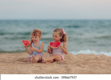 children eat ripe watermelon on the beach