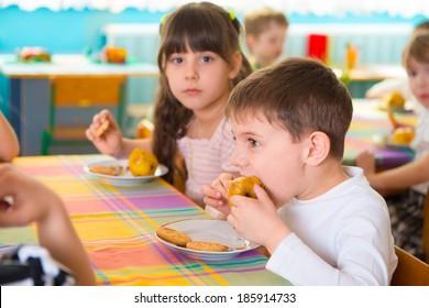 Children eating baked apple and cookie at kindergarten