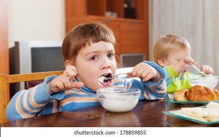 children eating dairy breakfast in home interior