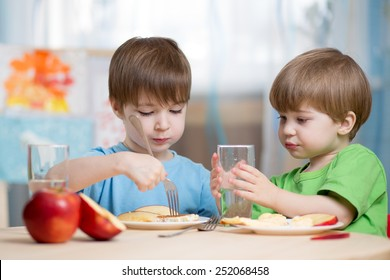 children eating  and drinking at home or kindergarten