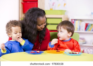 Children eating fruit at a nursery as their carer watches on