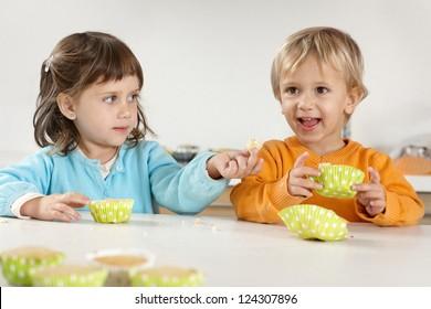 Children eating homemade muffins