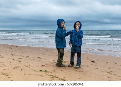 Children eating ice-cream on beach in England on a cold cloudy day