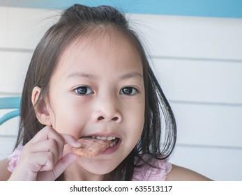 Children are eating snacks in the restaurant.