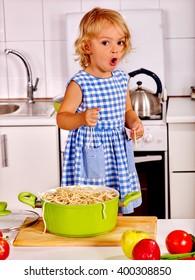 Children  eating spaghetti at kitchen. Kid cooking. Child safety in the kitchen.