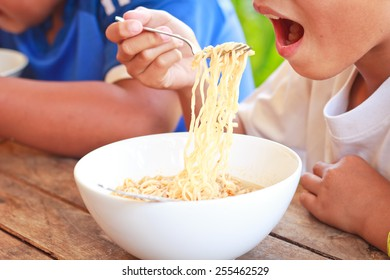 Children eating their  instant noodle in white bowl on wood table,Focused on instant noodle. Junk food