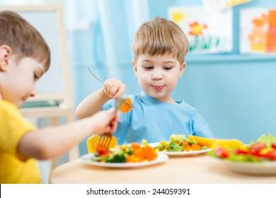 children eating vegetables in kindergarten or at home
