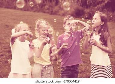 Children in elementary school age standing on green grass and blowing bubbles