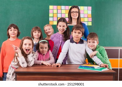 Children in elementary school posing with their teacher in front of chalkboard