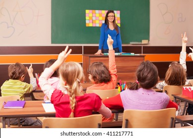 Children in elementary school are raised hand in classroom. Teacher is in the background in front of chalkboard.