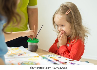 children engaged in creative work. Children sit at the table and draw watercolor. little girl feels surprisingly