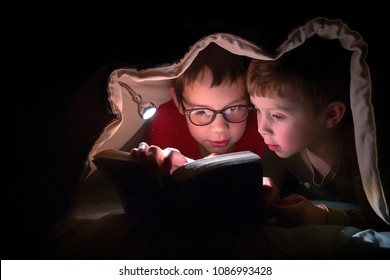 children engrossed in reading a book under the blanket. kids reading  in the bed with flashlight